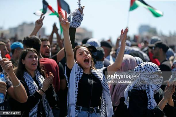 Palestinians protesting against Israel's occupation and its air campaign on the Gaza strip, shout slogans as they face Israeli troops near the...