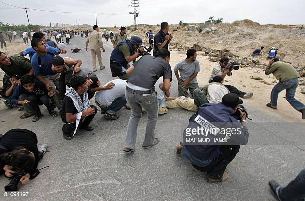 Palestinians protestors and journalists take cover as shots are fired by the Israeli military during a rally at the Erez crossing with Israeli in the...