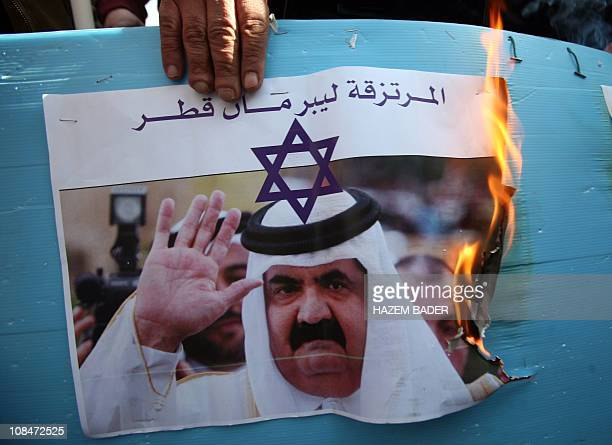Palestinians protestors burn a picture of Qatari Emir Sheikh Hamad bin Khalifa AlThani decorated with a Star of David during a demonstration in the...