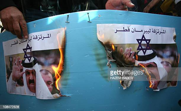 Palestinians protestors burn a picture of Qatari Emir Sheikh Hamad bin Khalifa AlThani during a demonstration in the West Bank city of Hebron on...