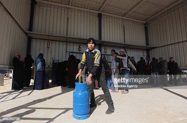 Palestinians queue up to get their propane cylinders refilled as Israel cuts the delivery of gas and fuel to the West Bank February 1 2014