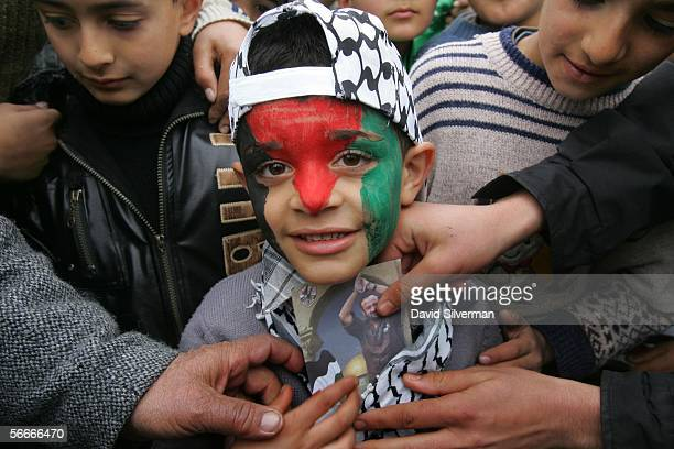 Palestinians reach for a campaign photo of Marwan Barghoutti that sixyearold Fatah supporter Fawwas Hammad Sawus keeps in his scarf while campaigning...