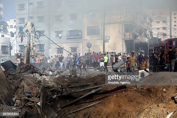 Palestinians react after Israeli airstrike hits a building belongs to Palestinian Abdulgafur family in Khan Yunis Gaza on July 29 2014