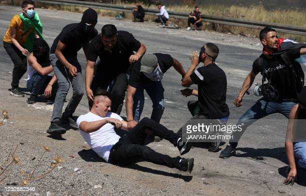 Palestinians react as a man falls after being injured, during confrontations with Israeli security forces near the Hawara checkpoint south of the...