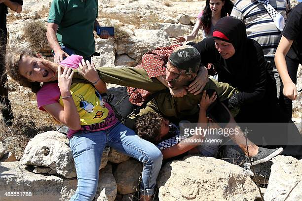 Palestinians react as an Israeli soldier attempts to arrest a Palestinian kid during the clashes following a protest against expropriation of...