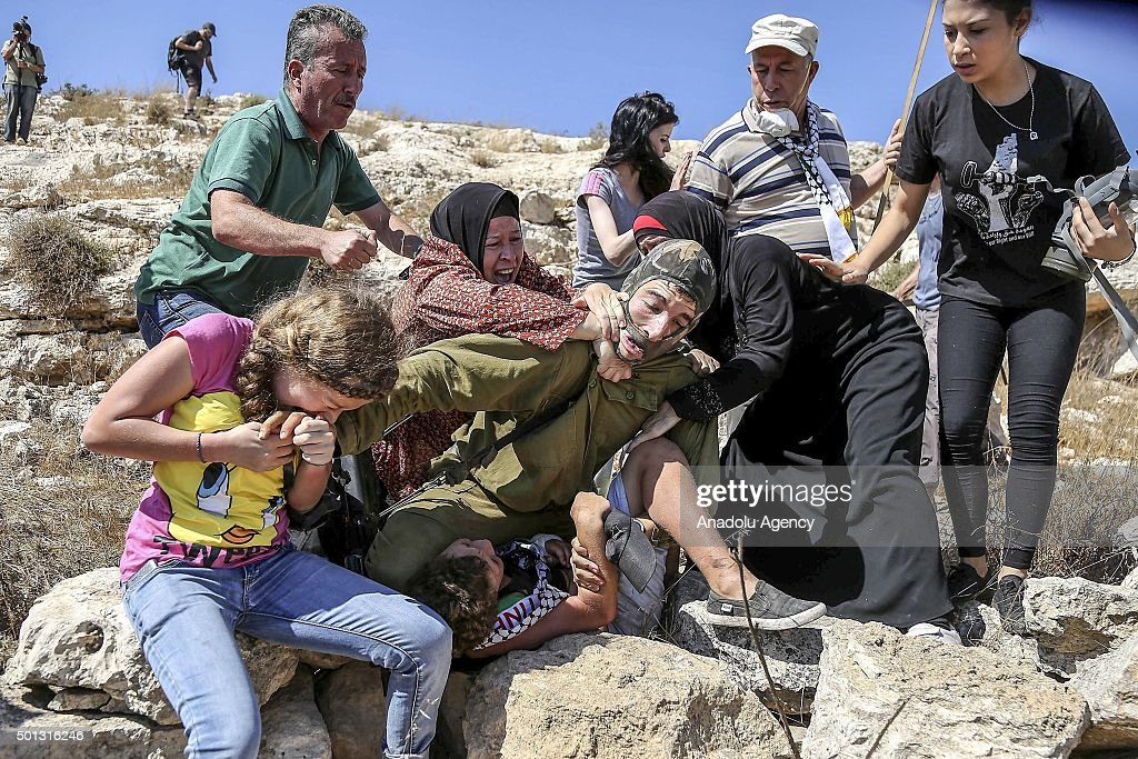 Palestinians react as an Israeli soldier attempts to arrest a Palestinian kid during the clashes following a protest against expropriation of Palestinian land by Israel and the Wall of Shame, the separation barrier between Israel and the West Bank, on August 28, 2015 in Nabi Saleh village, near the West Bank city of Ramallah.