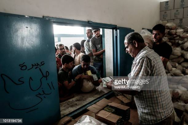 Palestinians receive aid at a United Nations food distribution centre in Jabalia refugee camp in the northern Gaza Strip on August 8, 2018.