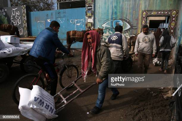 Palestinians receive food aid at a U.N. Relief and Works Agency warehouse in the Nuseirat refugee camp in central Gaza Strip.on January 17, 2018....