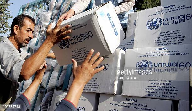 Palestinians receive food aid donated for refugees from the European Union and the World Food Programme and distributed by the United Nations Relief...