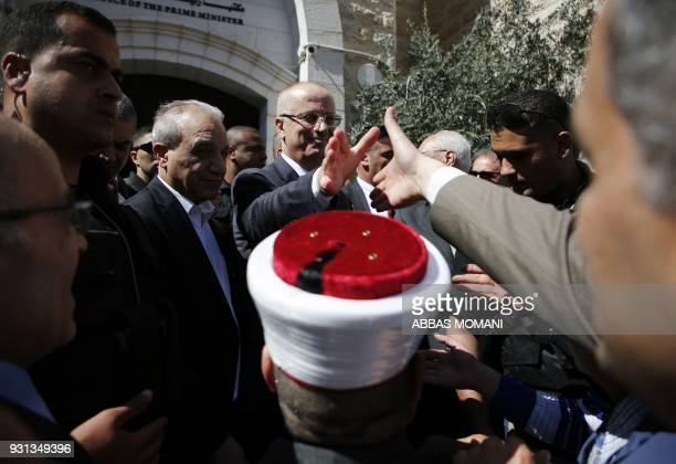 TOPSHOT Palestinians receive Prime Minister Rami Hamdallah in the West Bank town of Ramallah following his return from the Gaza Strip where an...