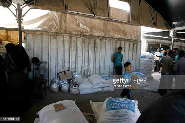Palestinians receive their monthly food aid at a United Nations distribution center in the Rafah refugee camp Southern Gaza Strip Palestinian...