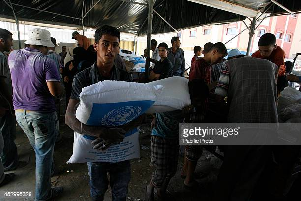 Palestinians receive their monthly food aid at a United Nations distribution center in the Rafah refugee camp, Southern Gaza Strip. Palestinian...