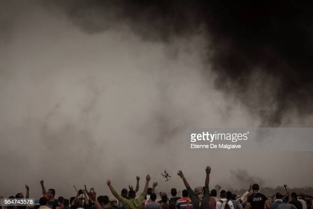 Palestinians rejoice as they watch an Israeli small drone overflying the protesters fails to the ground on May 4, 2018 in Khan Yunis, Gaza. Israeli...