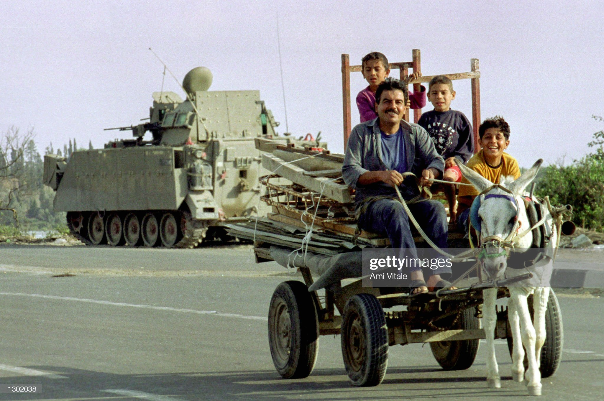 https://media.gettyimages.com/photos/palestinians-ride-a-by-an-israeli-tank-october-15-2000-in-netzarim-a-picture-id1302038?s=2048x2048