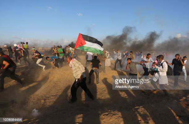 Palestinians run away from tear gas fired by Israeli forces on the 24th Friday of 'Great March of Return' demonstration near IsraelGaza border in...