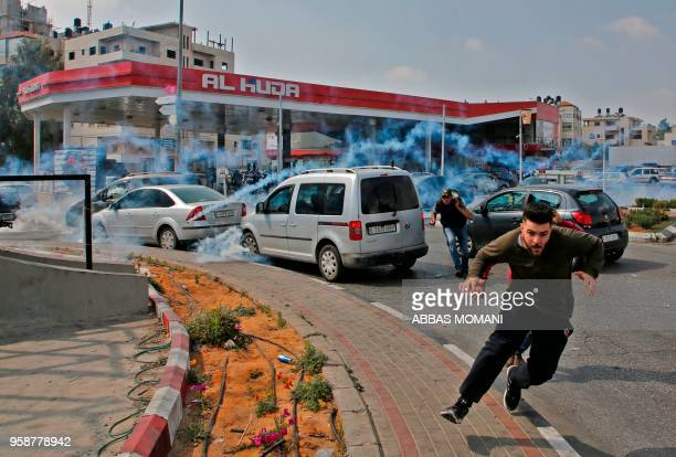TOPSHOT Palestinians run away from tear gas shot at them by Israeli forces during a protest in Ramallah in the occupied West Bank on May 15 2018...