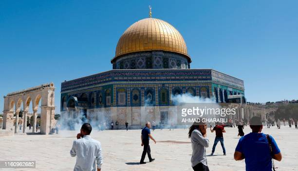 Palestinians run for cover from sound grenades fired by Israeli security forces outside the Dome of the Rock mosque in Jerusalem's AlAqsa Mosque...