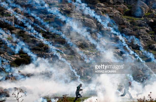 TOPSHOT Palestinians run for cover from tear gas during clashes with Israeli soldiers in the village of Mugheer about 25 kilometres northeast of the...