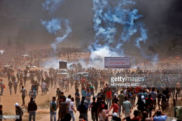 TOPSHOT Palestinians run for cover from tear gas during clashes with Israeli security forces near the border between Israel and the Gaza Strip east...