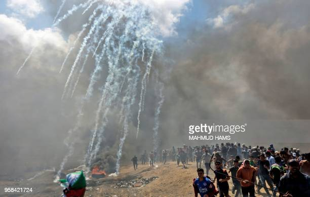 TOPSHOT Palestinians run for cover from tear gas fired by Israeli forces near the border between the Gaza strip and Israel east of Gaza City on May...