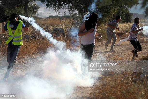 Palestinians run for cover from tear gas fired by Israeli security forces during a protest against Israeli assault on Gaza on July 31 2014 in...