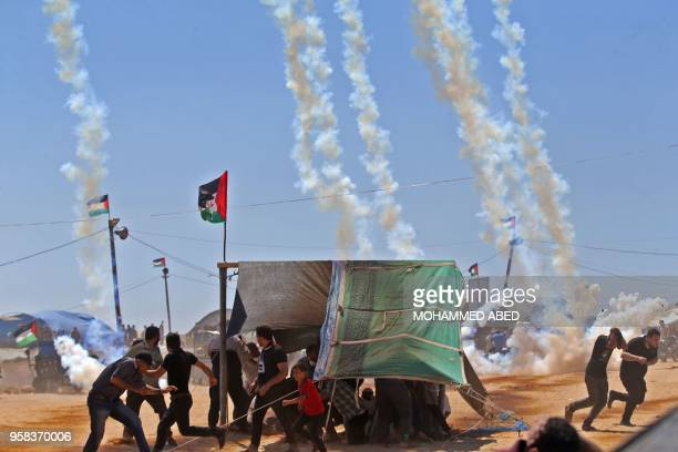 TOPSHOT Palestinians run for cover from tear gas near the border between Israel and the Gaza Strip east of Jabalia on May 14 as Palestinians protest...
