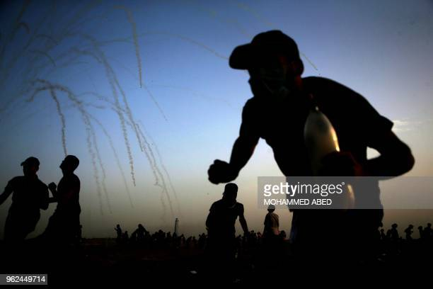 TOPSHOT Palestinians run for cover from tear gas shot by Isreali forces during a demonstration along the border between Israel and the Gaza strip...