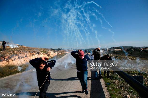 TOPSHOT Palestinians run for covers from smokegrenades during clashes with Israeli security forces following a demonstration in support of...