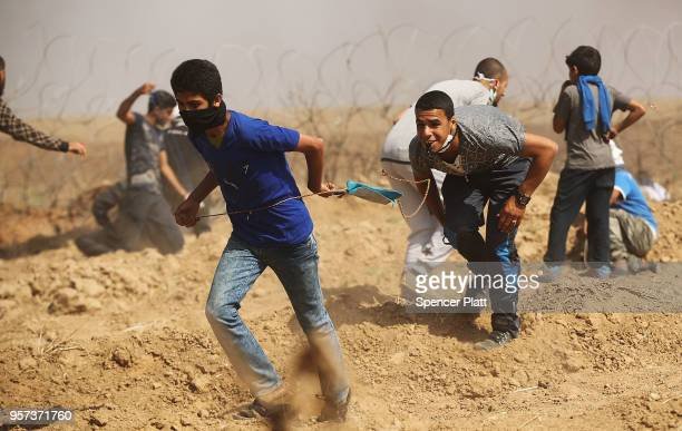 Palestinians run from tear gas as they gather at border fence with Israel as mass demonstrations at the fence continue on May 11 2018 in Gaza City...