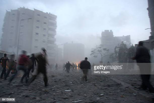Palestinians run towards the destroyed home of a Hamas military leader after an Israeli missile strike on December 29 2008 in Beit Lahia Gaza Strip...