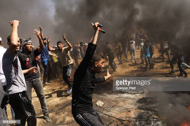 Palestinians rush to the border fence with Israel as mass demonstrations at the fence continue on May 14 2018 in Gaza City Gaza Israeli soldiers...