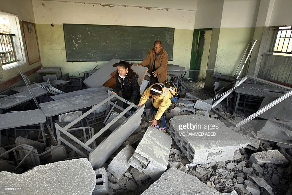 Palestinians school girls climb over the rubble in a classroom, damaged during last week's Israeli offensive, at their school in Gaza City, on November 24, 2012, three days after a truce was declared between Israel and Hamas. Gaza's children, virtually absent from the streets since the violence, are beginning to return to school after a truce between Israel and Gaza's Hamas rulers ended eight days of deadly bombardment.