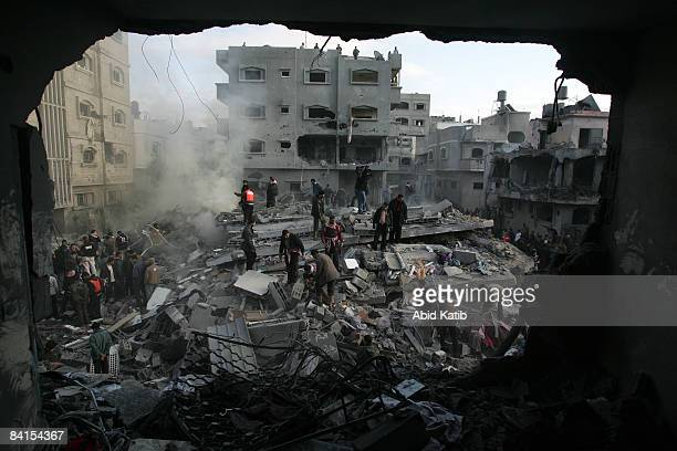 Palestinians search for bodies in the rubble of the destroyed house of Hamas senior leader Nizar Rayan after an Israeli missiles strike in the...