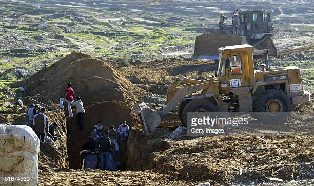 Palestinians search in the rubble of a collapsed smuggling tunnel linking the Gaza Strip with Egypt December 17 2004 in the Rafah refugee camp Gaza...