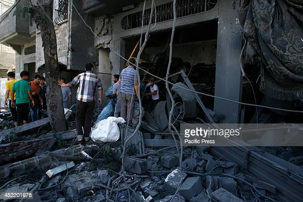 Palestinians search through the rublle of a destroyed house following an Israeli missile strike, in Rafah in the southern Gaza Strip. Israel said it...