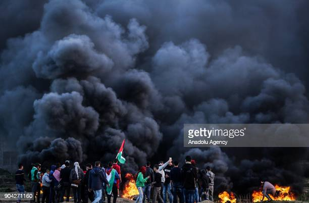 Palestinians set tires on fire after Israeli security forces' intervention during a protest against US decision to recognize Jerusalem as Israel's...