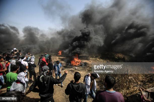 Palestinians set tires on fire during a protest organized within the 'Great March of Return' despite Israel's threats near the Israeli border in Gaza...