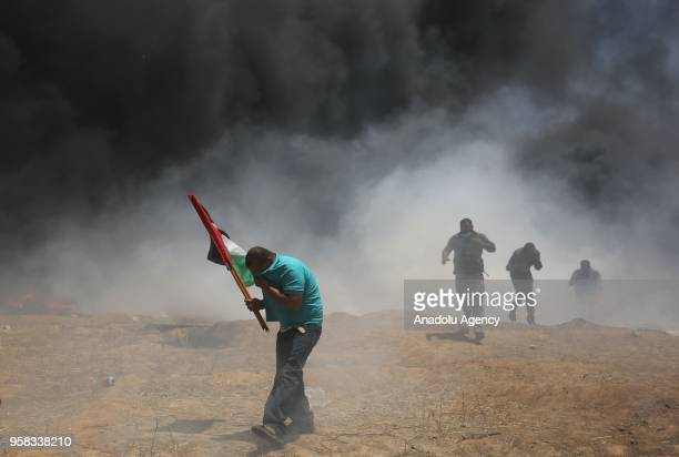 Palestinians set tires on fire in response to Israel's intervention during a protest organized to mark 70th anniversary of Nakba also known as Day of...