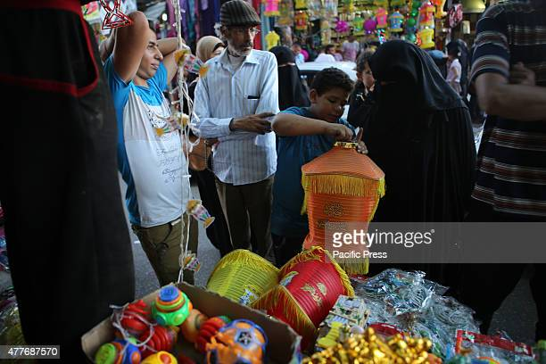 Palestinians shop in a market during the advance celebration of the Muslim holy month of Ramadan in Rafah in the southern Gaza Strip
