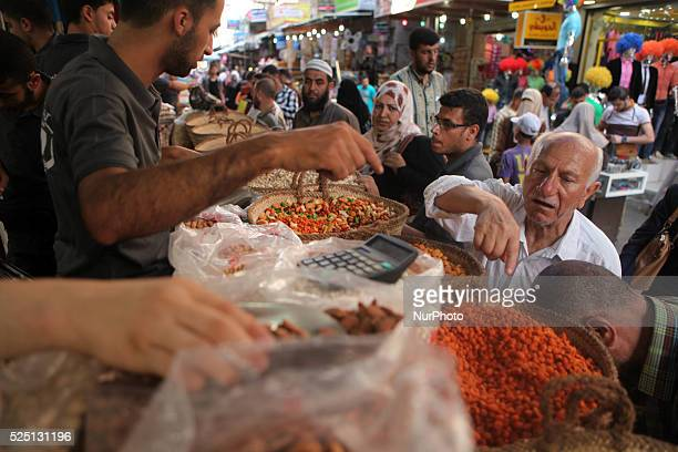 Palestinians shop in a market for the Eid alFitr a threeday holiday that marks the end of the fasting month of Ramadan in Gaza city on July 15 as...