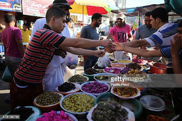 Palestinians shop in a street market on the fifth day of the holy month of Ramadan in Rafah in the southern Gaza Strip on June 22 2015