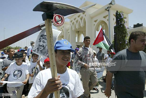 Palestinians shout anti Israel slogans during a protest as they hold a poster of their leader, a hoe and their national flag on June 22, 2003 at Gaza...