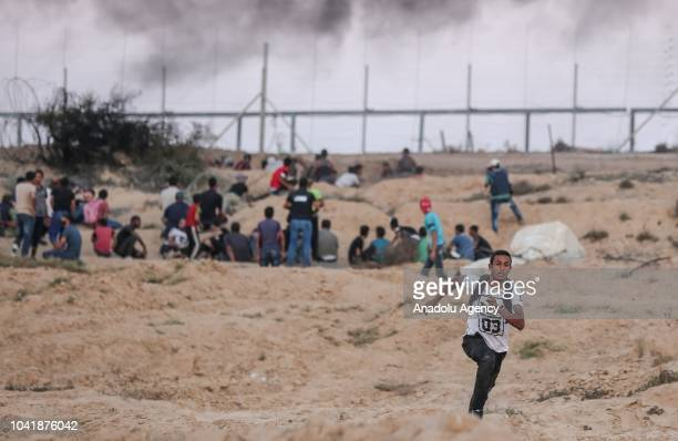 "Palestinians shout slogans after Israeli intervention with tear gas canisters during the ""Great March of Return"" demonstration at the Israeli border..."