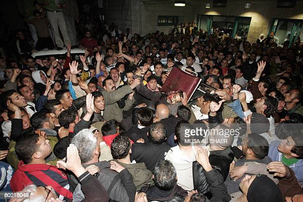 Palestinians shout slogans as they gather around the body of Islamic Jihad leader Mohammed Shahada after he was killed by Israeli undercover forces...