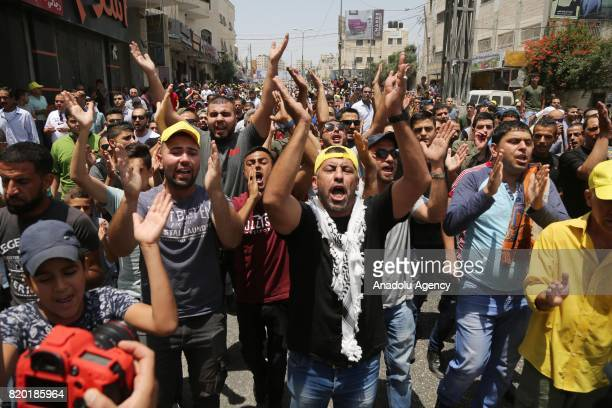 Palestinians shout slogans as they stage a demonstration to protest Israeli violations and restrictions on Al Aqsa Mosque at Qalandiya checkpoint in...