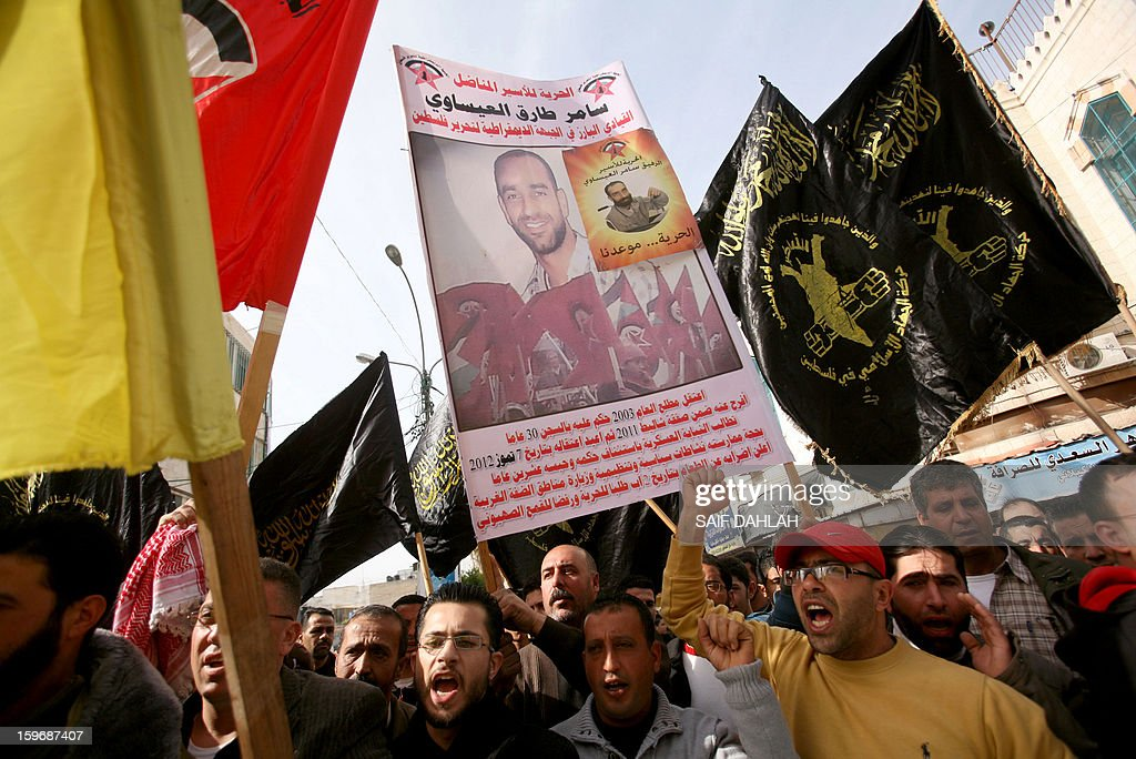 Palestinians shout slogans as they wave flags of the Palestinian Islamic Jihad Movement (R) and hold pictures of relatives and individuals detained in Israeli prisons during a demonstration in the West Bank city of Jenin on January 18, 2013, in support with Palestinians on hunger strike in Israeli jails and against administrative detention.