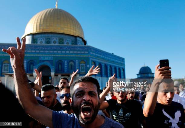 Palestinians shout slogans in front of the Dome of the Rock at the alAqsa mosque compound in the Jerusalem's Old City on July 27 after the site was...