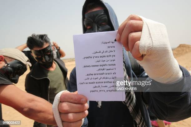 Palestinians show leaflets that will be attached to a kite before trying to fly it over the border fence with Israel in Rafah in southern Gaza Strip...