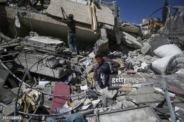 Palestinians sift through the rubble of a building destroyed during an Israeli airstrike, three days after an Egypt-brokered cease fire agreement, on...