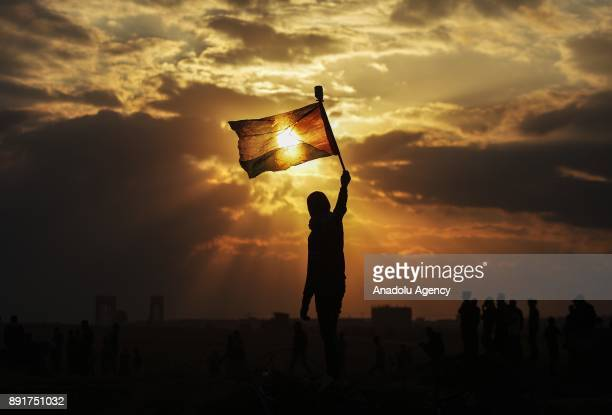 Palestinian's silhoutte is seen as he holds a Palestinian flag during a protest against US President Donald Trump's announcement to recognize...